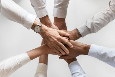 Group of hands stacking on top of each other.
