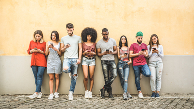 Group of young adults standing against a wall using their cell phones.