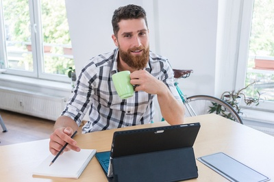 Man drinking a cup of coffee while working.