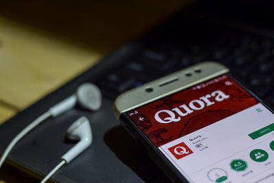 Phone with Quora app displayed.