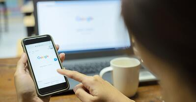 Person Searching on Google on a Phone and Desktop