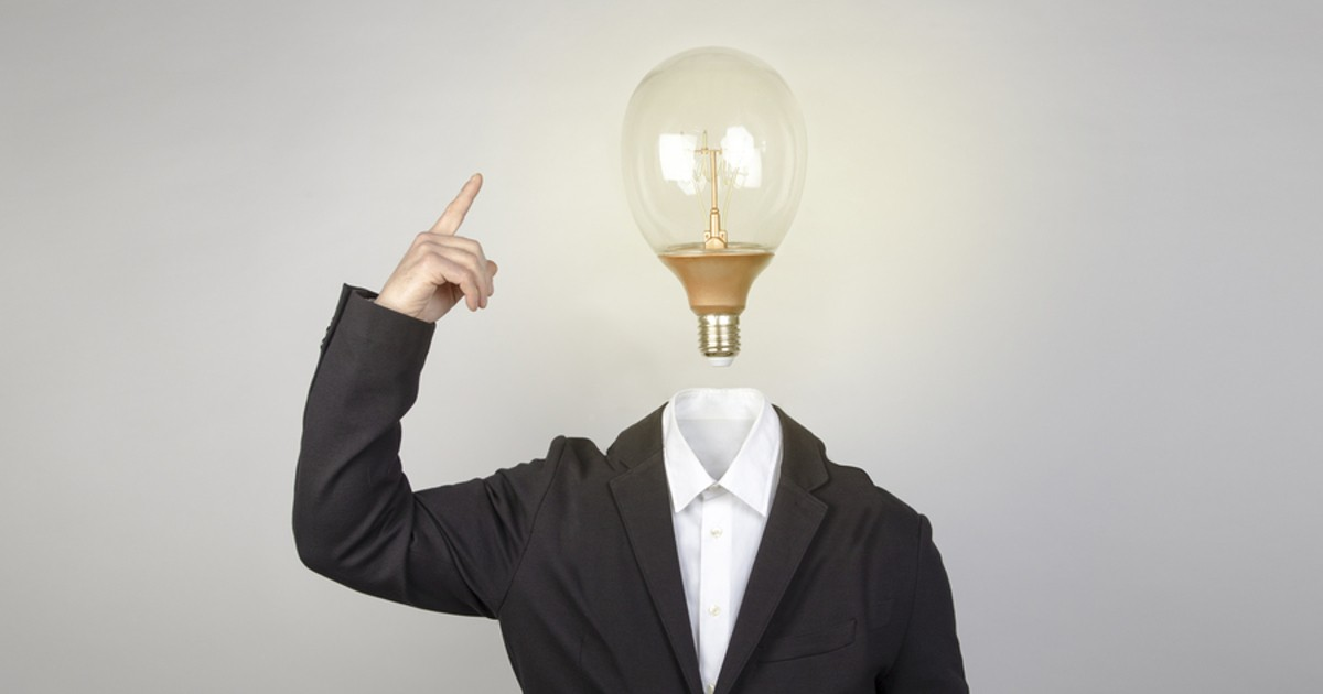 Person standing with a lightbulb in place of a head.