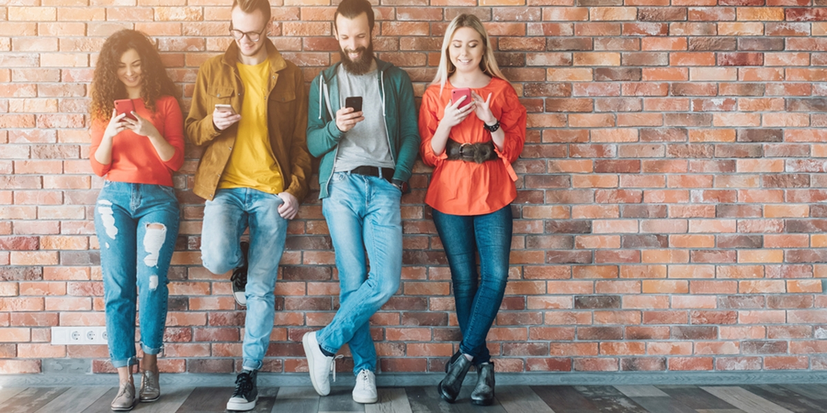 Group of young adults standing against a well looking at their phones.