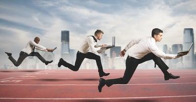 3 Men holding laptops running a foot race