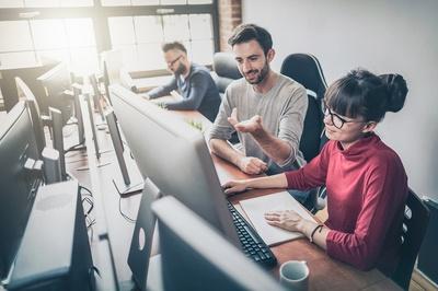 Three people sitting in front of desktop computers talking.